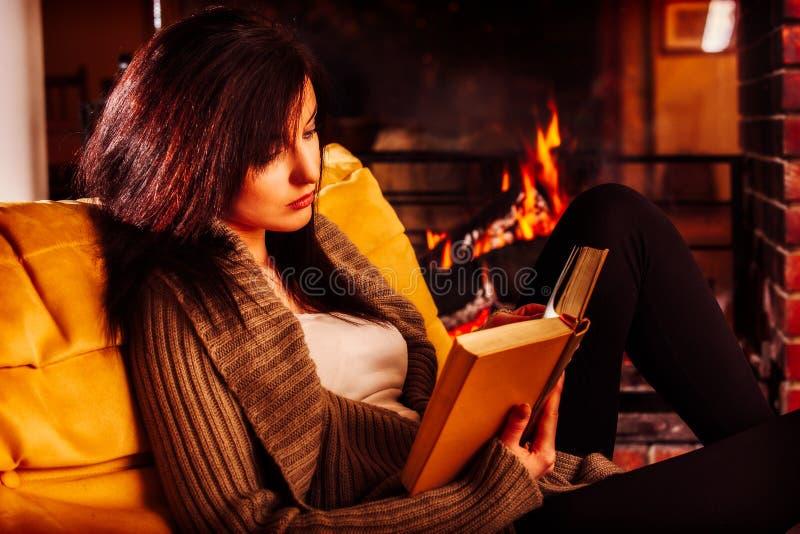 Jonge vrouw die een boek lezen door open haard stock foto's