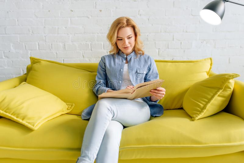 Jonge vrouw die een boek op comfortabele gele laag lezen stock afbeeldingen
