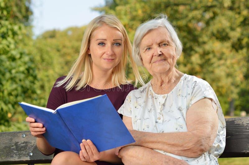 Jonge vrouw die een boekbejaarde lezen stock afbeeldingen