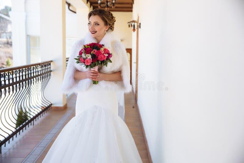 Jonge vrouw die een boeket die van roze en rode rozen houden en de afstand onderzoeken, ruim glimlachen Een meisje met helder stock fotografie