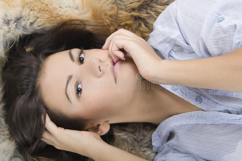 Jonge vrouw die in een bont ligt royalty-vrije stock foto