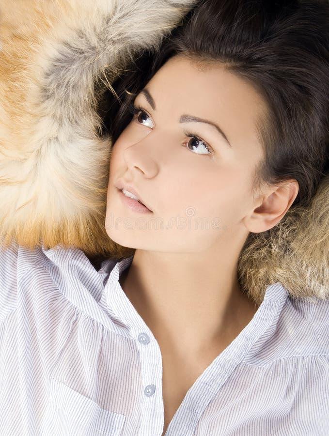 Jonge vrouw die in een bont ligt royalty-vrije stock afbeelding