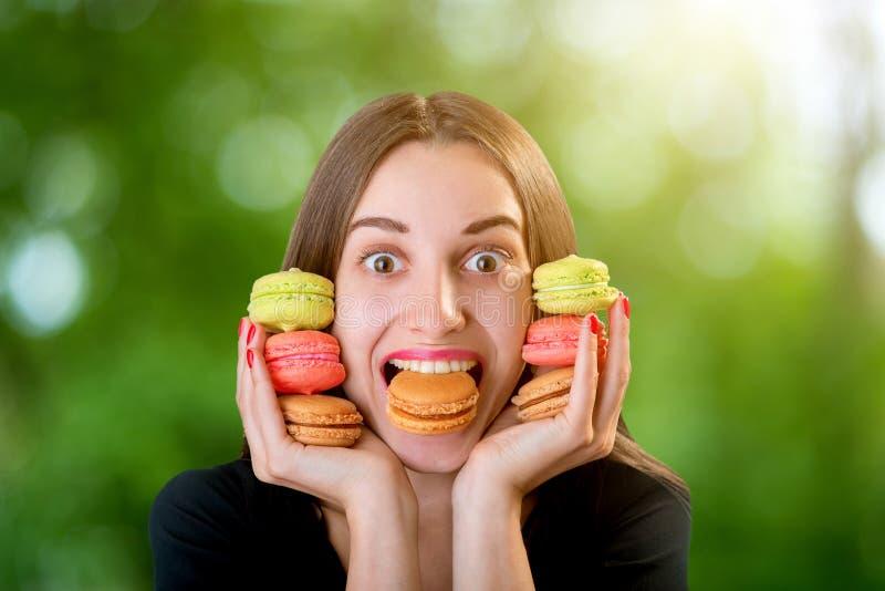 Jonge vrouw die een bos van kleurrijke makarons houden rond haar fac royalty-vrije stock foto's