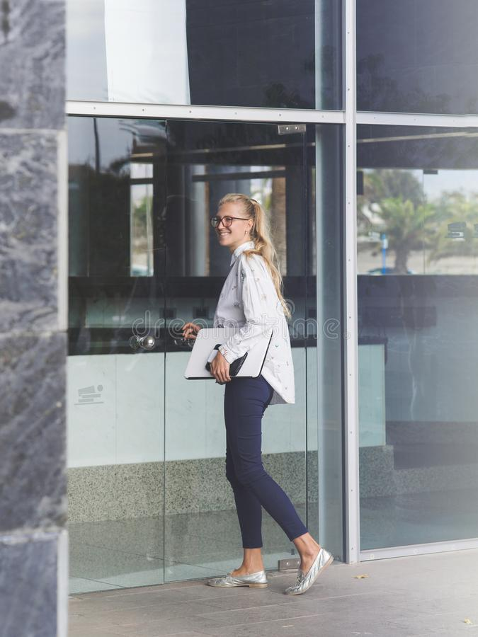 Jonge vrouw die een bureaugebouw ingaan royalty-vrije stock afbeelding