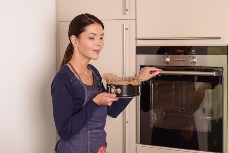 Jonge vrouw die een cake plaatsen in de oven royalty-vrije stock foto