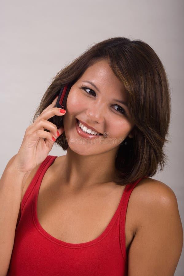 Jonge vrouw die een celtelefoon uitnodigt stock fotografie