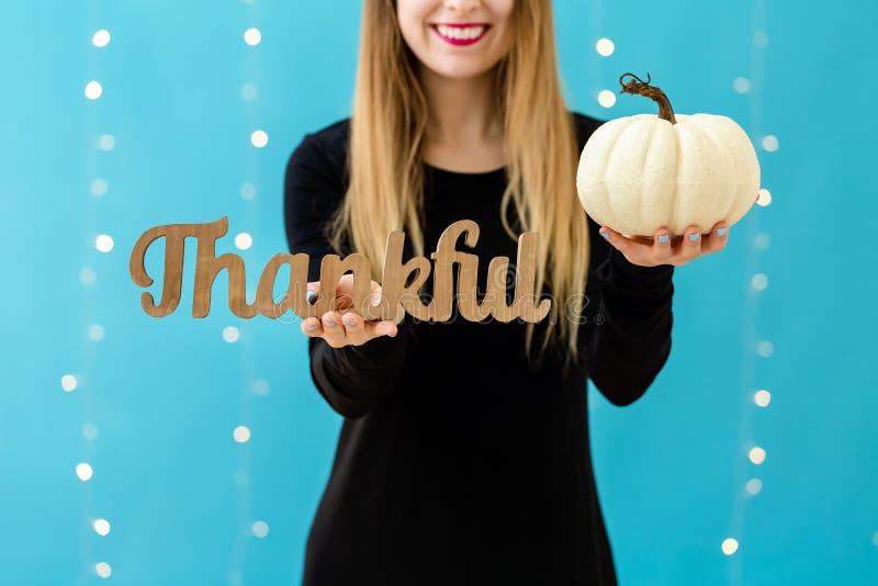 Jonge vrouw die een dankbaar blok en een pompoen houden stock foto's