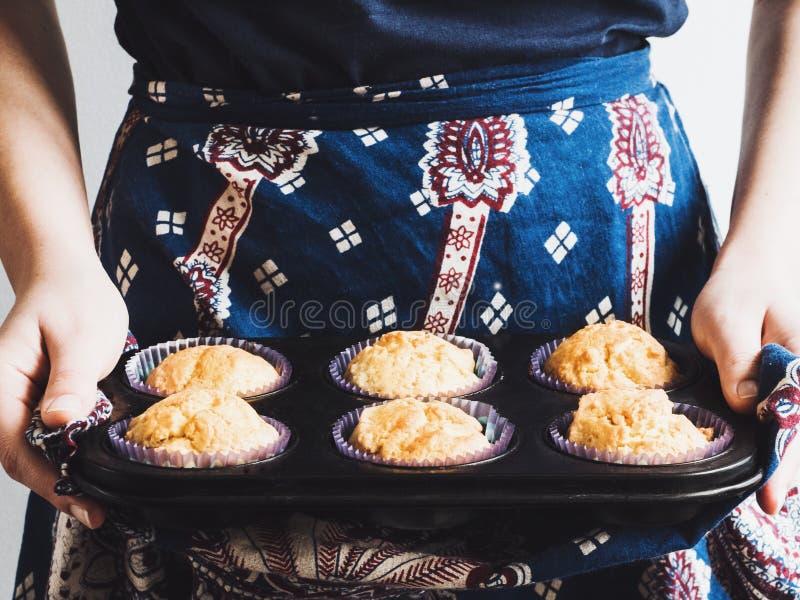 Jonge vrouw die een dienblad van geurige cupcakes houden stock afbeelding