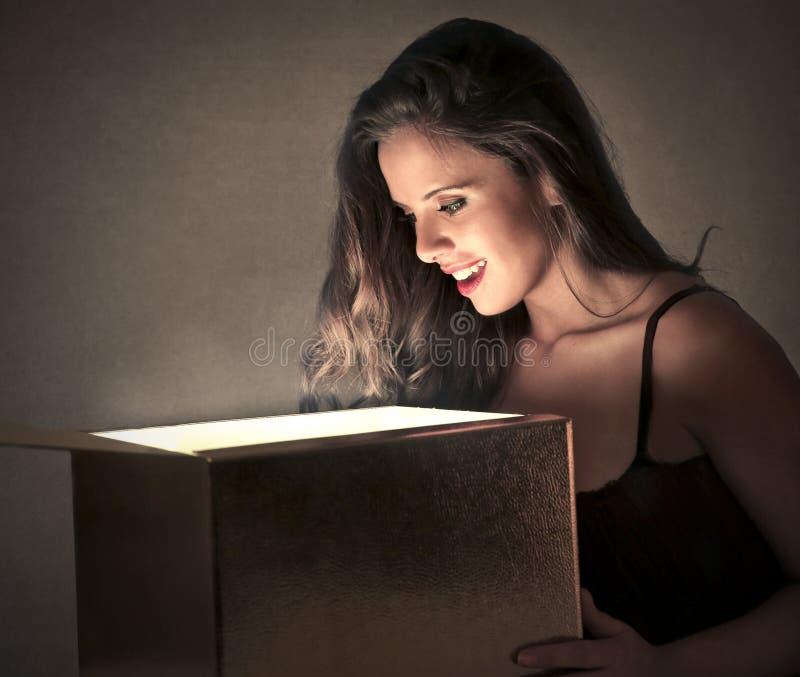 Jonge vrouw die een doos onderzoeken stock afbeeldingen