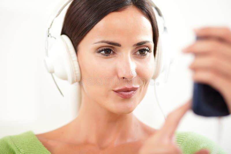 Download Jonge Vrouw Die Een Draagbare Muziekspeler Met Behulp Van Stock Afbeelding - Afbeelding bestaande uit voorgrond, draagbaar: 54076113