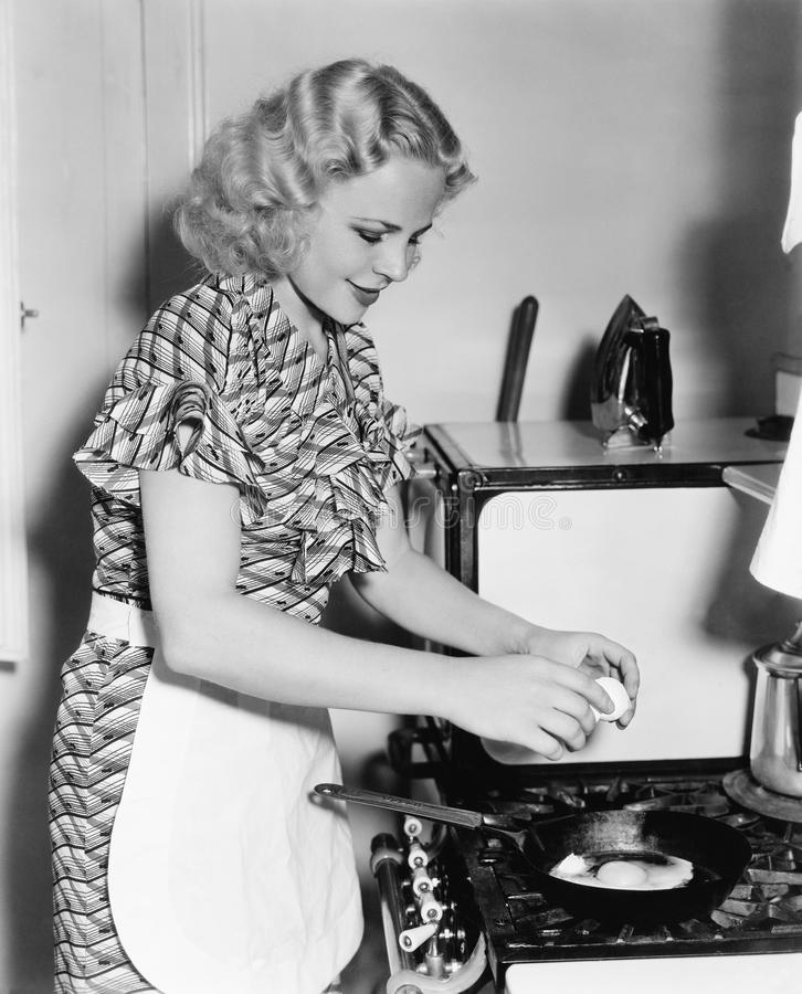 Jonge vrouw die een ei breken in een pan (Alle afgeschilderde personen leven niet langer en geen landgoed bestaat Leverancierswar royalty-vrije stock fotografie