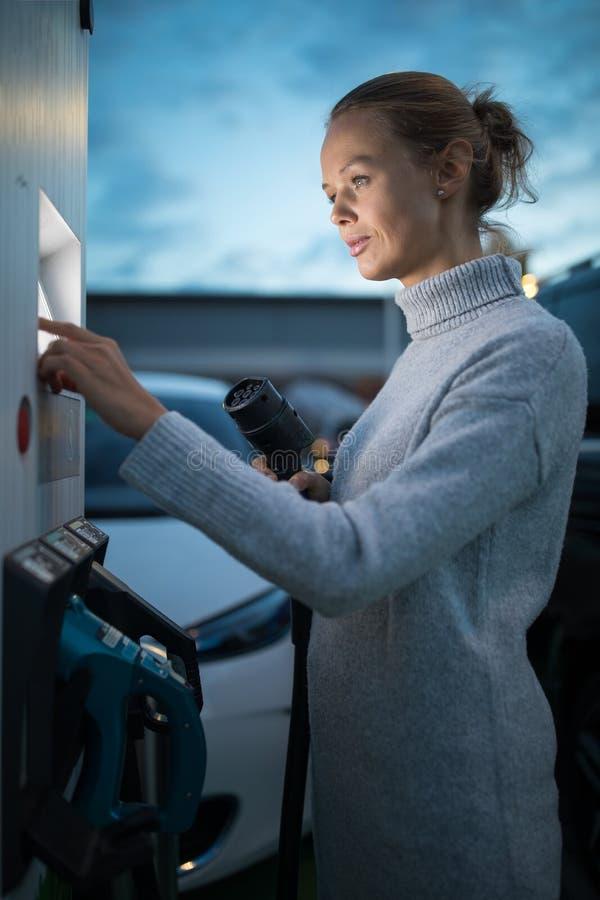 Jonge vrouw die een elektrisch voertuig laden stock foto's