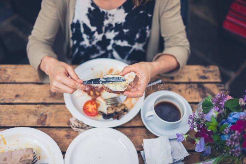 Jonge vrouw die een Engels ontbijt hebben stock foto's