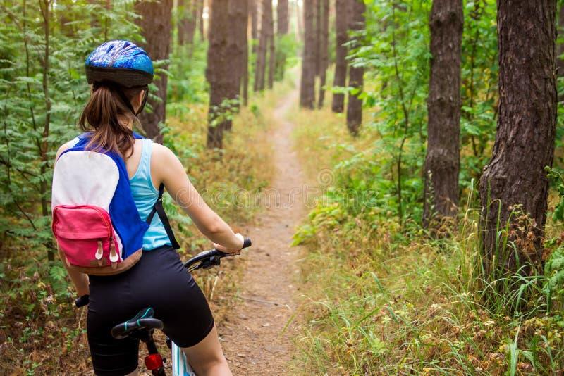 Jonge vrouw die een fiets in het bos berijden royalty-vrije stock afbeelding