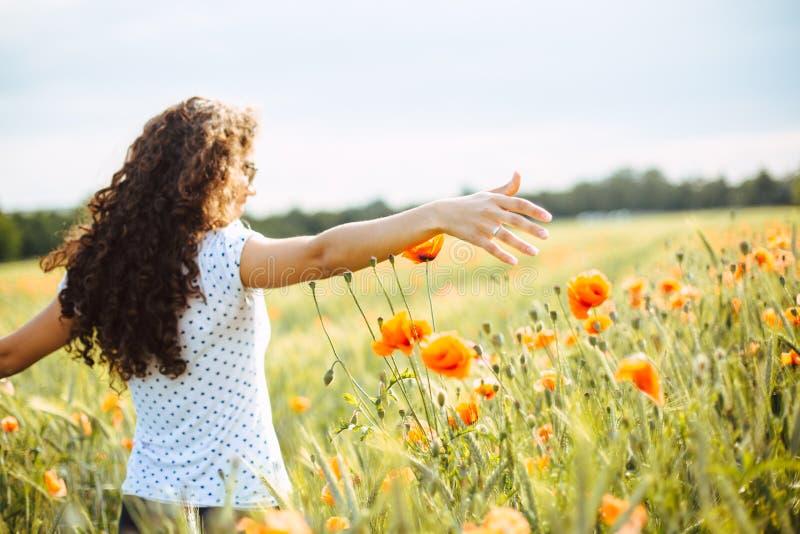 Jonge vrouw die een gebied van wildflowers doornemen stock foto's