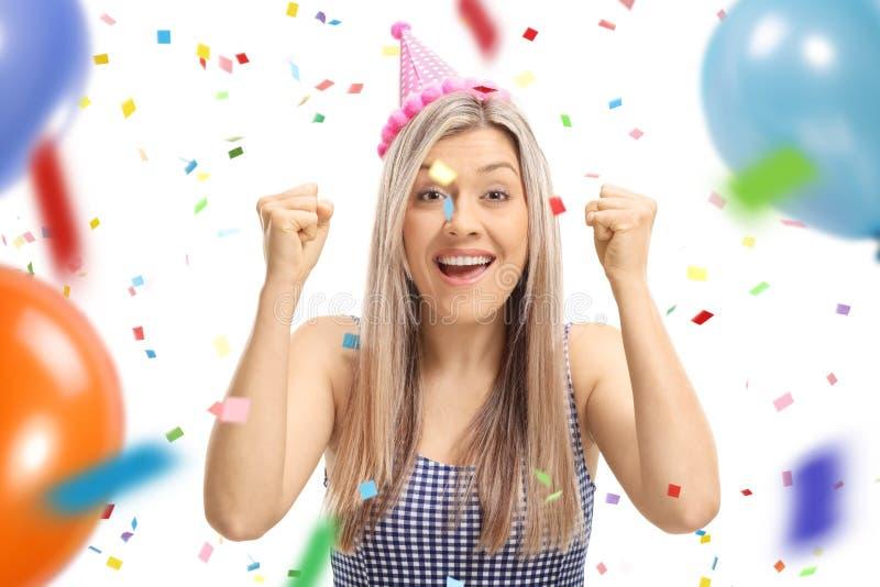 Jonge vrouw die een gesturing geluk van de partijhoed met confett dragen stock afbeelding