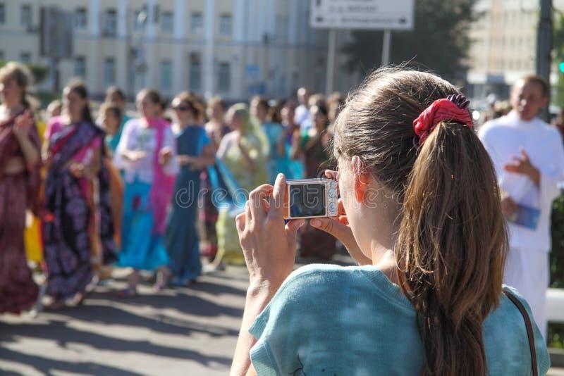 Jonge vrouw die een groep hazen Krishna fotografeert royalty-vrije stock afbeelding