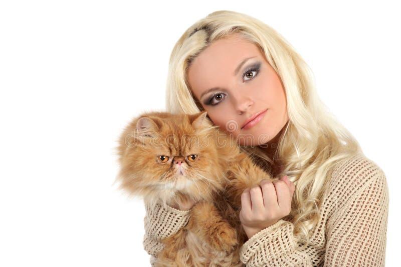 Jonge vrouw die een grote zachte rode kat koesteren stock foto