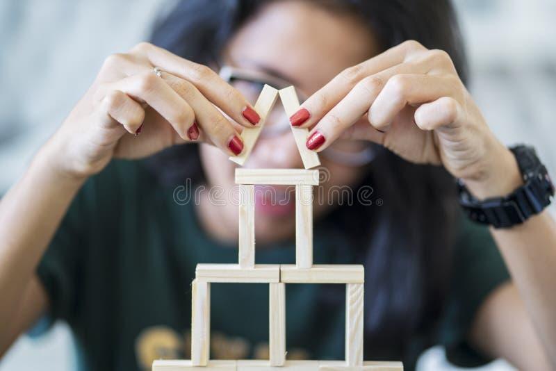 Jonge vrouw die een houten blokkenhuis maken stock afbeelding