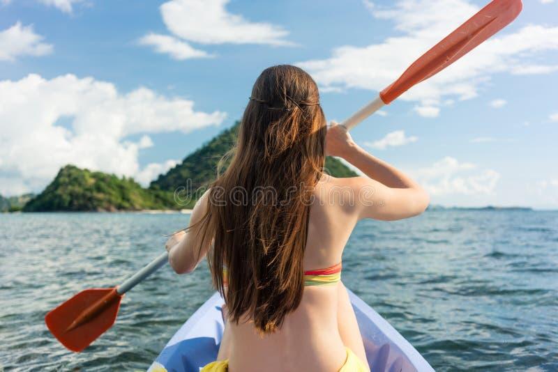 Jonge vrouw die een kano op het overzees paddelen tijdens de zomervakantie i royalty-vrije stock foto