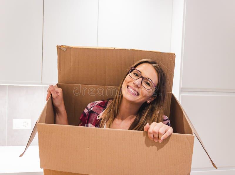 Jonge vrouw die in een kartondoos glimlachen stock afbeeldingen