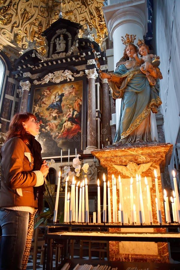 Jonge vrouw die in een kerk bidden stock fotografie