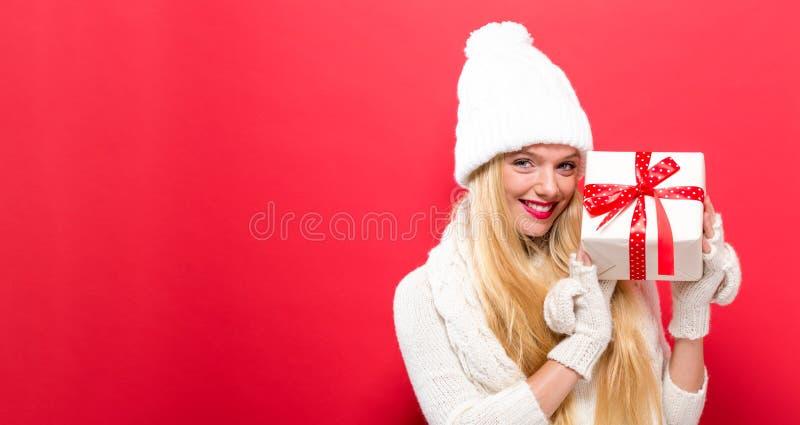 Jonge vrouw die een Kerstmisgift houden stock foto's