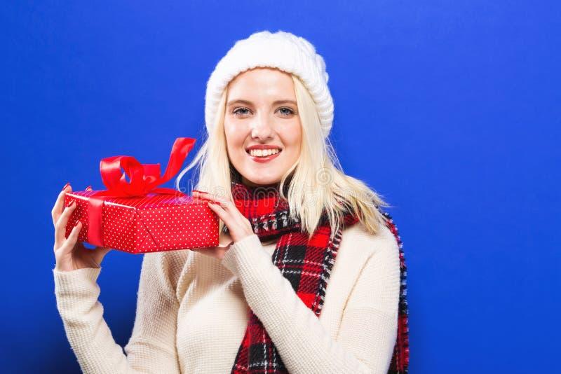 Jonge vrouw die een Kerstmisgift houden royalty-vrije stock afbeeldingen