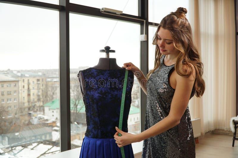 Jonge vrouw die een kleding op een ledenpop, naaister in werkruimte proberen stock afbeelding