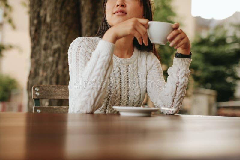 Jonge vrouw die een kop van koffie houden bij koffie stock afbeelding