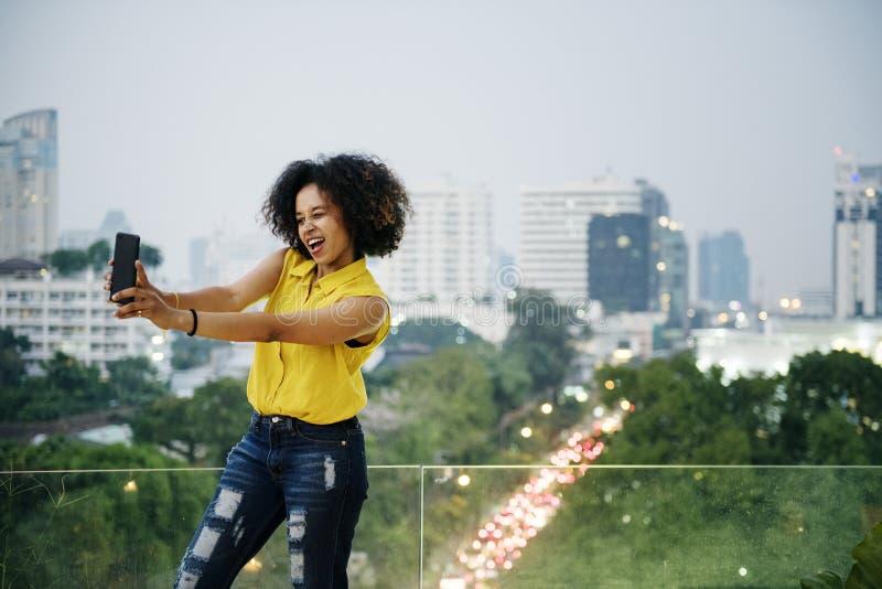 Jonge vrouw die een leuke selfie in cityscape nemen royalty-vrije stock foto's