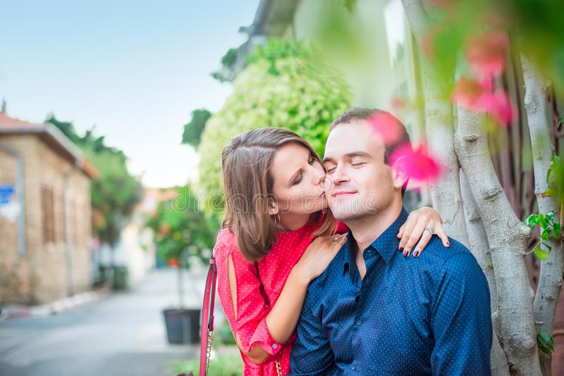 Jonge vrouw die een man op wang kussen Daling van liefde romantisch echtpaar in heldere kleren op de straat met bloeiende bomen F stock afbeeldingen