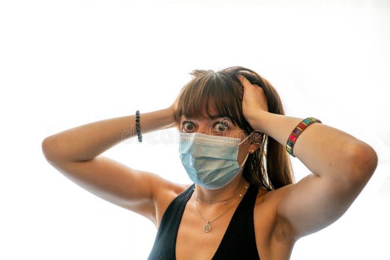 Jonge vrouw die een medisch gezichtsmasker draagt, lichaamstaal die gestrest is door zelfisolatie in tijden van het Coronavirus royalty-vrije stock fotografie