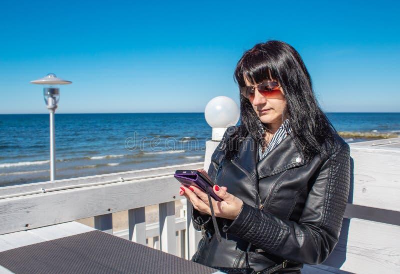 Jonge vrouw die een mobiele smartphone gebruiken stock afbeelding