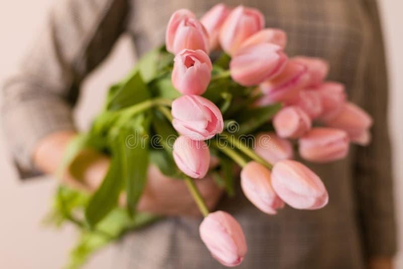 Jonge vrouw die een mooie bos van tulpen in haar handen houden De lente huidig voor een meisje in een grijze kleding Het boeket v royalty-vrije stock foto