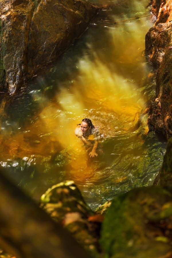 Jonge vrouw die in een natuurlijke tropische pool zwemmen royalty-vrije stock afbeeldingen