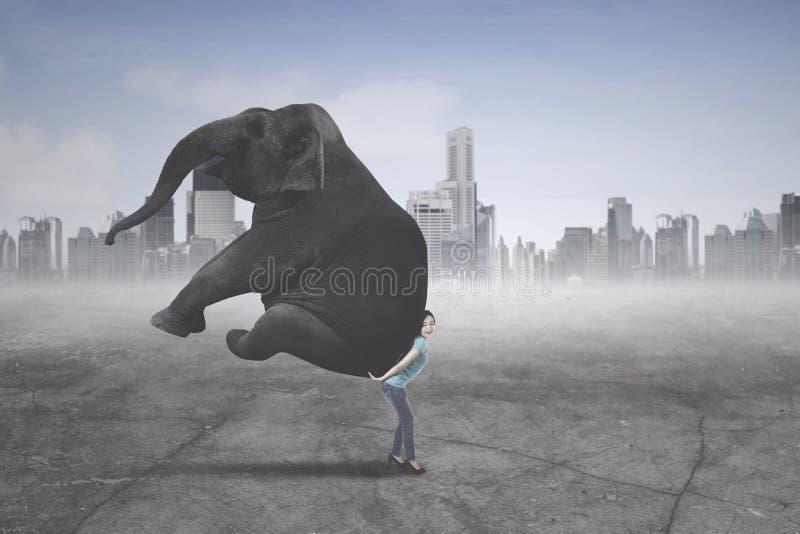 Jonge vrouw die een olifant dragen stock afbeeldingen