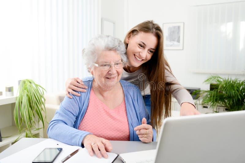 Jonge vrouw die een oude hogere vrouw helpen die administratie en administratieve procedures met laptop computer thuis doen stock afbeeldingen