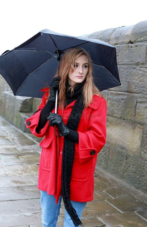 Jonge vrouw die een paraplu van ijzel en regen houden stock foto's