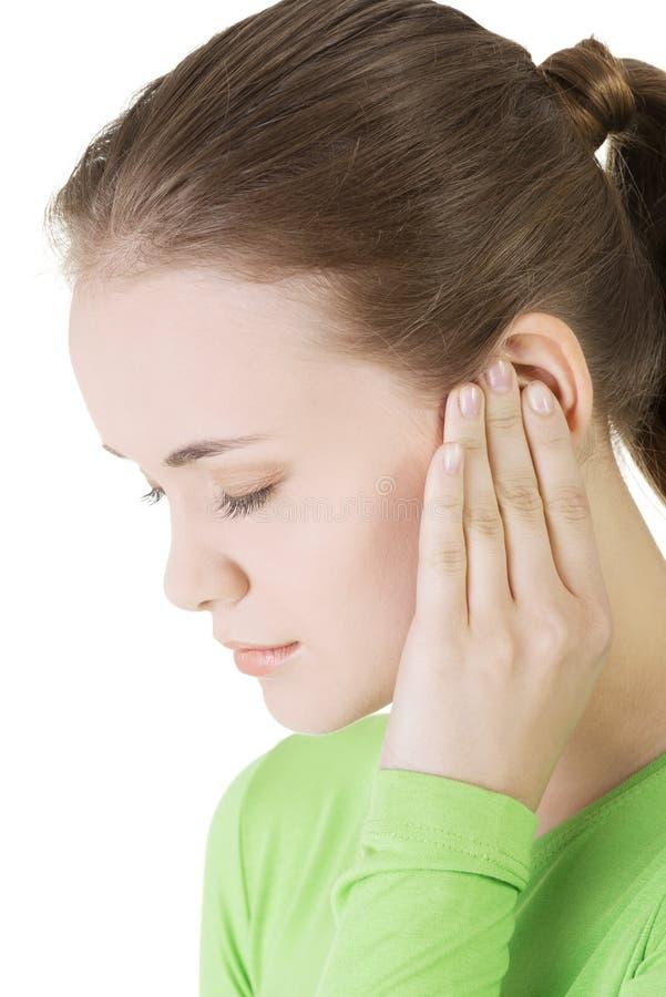 Jonge vrouw die een pijn in oor voelen stock foto