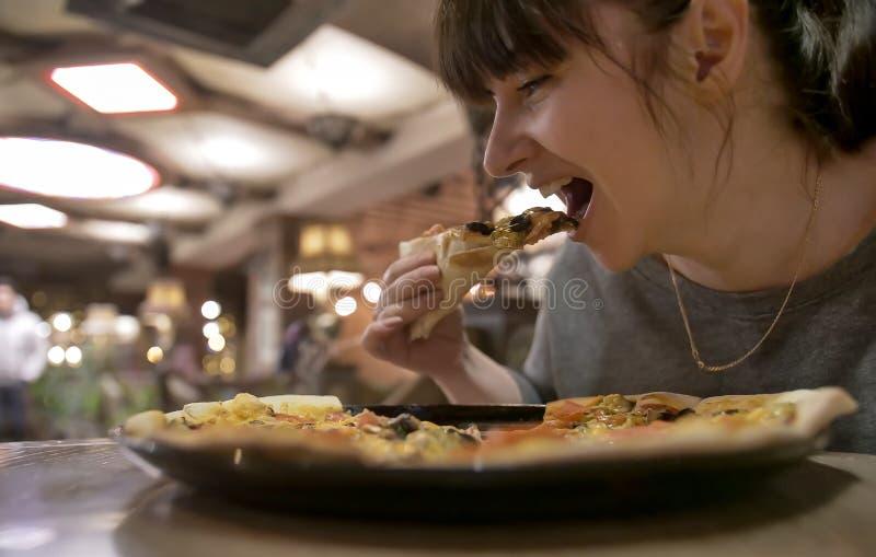 Jonge vrouw die een plak van pizzazitting eten in een koffie, close-up royalty-vrije stock foto's