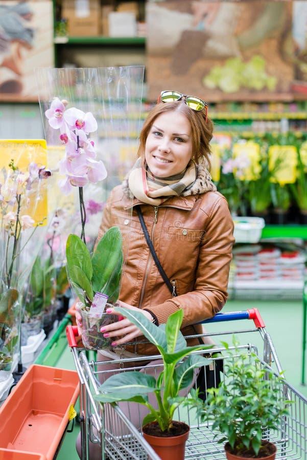 Jonge vrouw die een pot van bloemen houden stock afbeeldingen