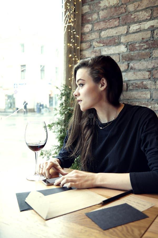 Jonge vrouw die in een restaurant met rode wijn werken royalty-vrije stock fotografie