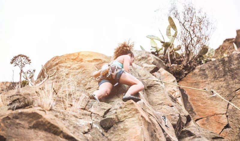 Jonge vrouw die een rotswand beklimt in een canyon - Een sterke klimbertraining in de buitenlucht - Reis, adrenaline en extreme g royalty-vrije stock afbeelding