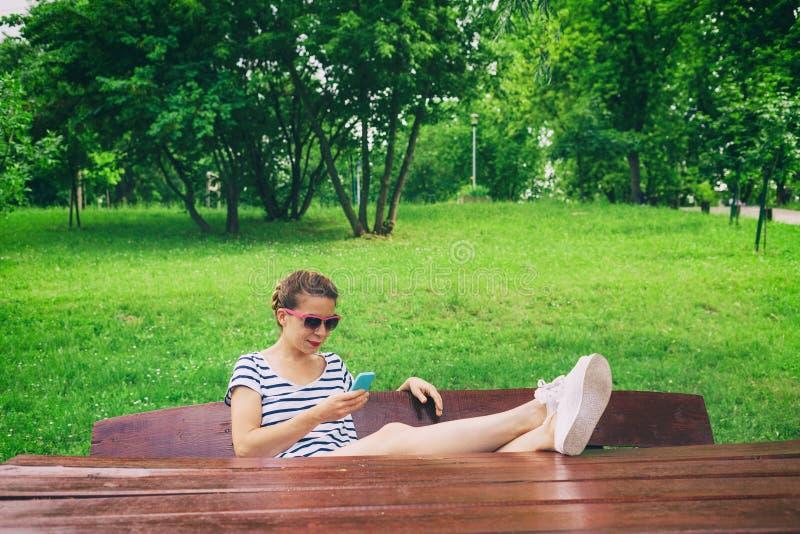 Jonge vrouw die een smartphone gebruikt stock foto
