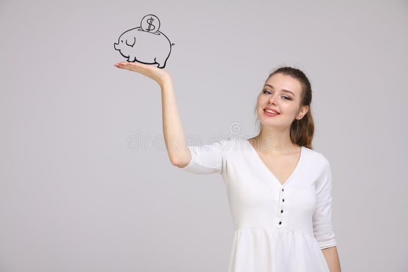 Jonge vrouw die een spaarvarken trekken stock foto