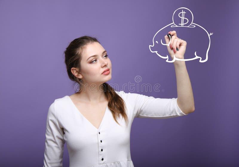 Jonge vrouw die een spaarvarken trekken stock afbeeldingen