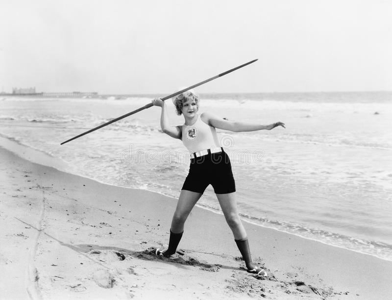 Jonge vrouw die een speer op het strand voorbereidingen treffen te werpen (Alle afgeschilderde personen leven niet langer en geen stock foto