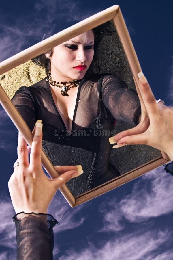 Jonge vrouw die een spiegel wordt overdacht royalty-vrije stock foto