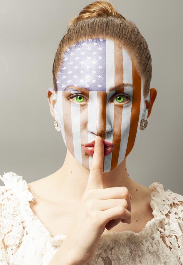 Jonge vrouw die een stiltegebaar met de vlag van de V.S. maken royalty-vrije stock fotografie